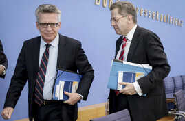 German Interior Minister Thomas de Maiziere, left, and Hans-George Maassen, head of Germany's domestic intelligence agency BfV, leave after a press conference in Berlin, July 4, 2017.