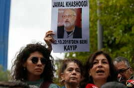 Activists, members of the Human Rights Association Istanbul branch, holding posters with photos of missing Saudi journalist Jamal Khashoggi, talk to members of the media, during a protest in his support near the Saudi Arabia consulate in Istanbul, Oc