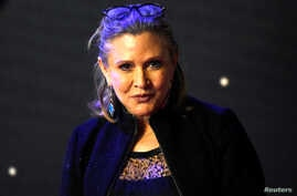 "FILE: Carrie Fisher poses for cameras as she arrives at the European Premiere of ""Star Wars, The Force Awakens"" in Leicester Square, London, Dec. 16, 2015."