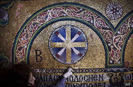 A restoration expert works on a mosaic inside the Church of the Nativity, in the West Bank city of Bethlehem, Feb. 4, 2016.