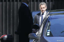 Former French President Nicolas Sarkozy (R) leaves his residence in Paris, July 2, 2014.