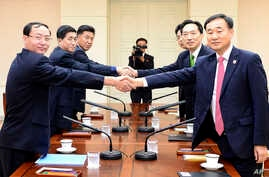 South Korea's chief delegate Lee Deok-haeng, second from right, shakes hands with North Korean counterpart Pak Yong Il, second from left, before the Inter-Korean Red Cross working level meeting at Panmunjom in Paju, South Korea, Sept. 7, 2015.