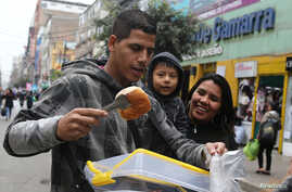 FILE - Bryant Medina, a migrant from Venezuela, sells traditional Venezuelan pastry known as bombas venezolanas at the La Victoria district in Lima, Peru, Aug. 23, 2017.
