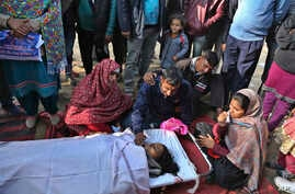 Relatives of an Indian woman who was killed in Pakistani firing and shelling wail over her body at a hospital in the Ranbir Singh Pura district of Jammu and Kashmir, India, Jan. 19, 2018.