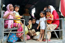 Ethnic Rohingya women and children whose boats were washed ashore on Sumatra Island board a military truck to be taken to a temporary shelter in Seunuddon, Aceh province, Indonesia, May 10, 2015.