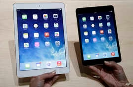 An Apple employee demonstrates the new iPad Air, left and iPad mini, Oct. 22, 2013, in San Francisco.