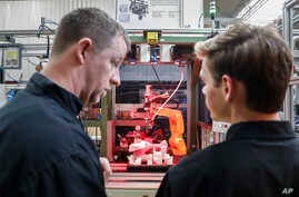 FILE - A.J. Scherman, 37, left, works with fellow apprentice Ryan Buzzy on a robotics control computer at a chainsaw assembly line at a Stihl Inc. production plant in Virginia Beach, Va.. May 25, 2017.