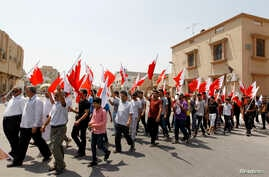 Anti-government protesters holding Bahraini flags march along the streets of the village of Saar during an anti-government protest, west of Manama, Aug. 14, 2013.