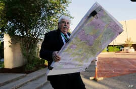Russ Tidwell, a former lobbyist who is helping minority rights groups sue Texas over Republican-drawn voting maps holds a set of maps as he makes his way to the federal court house, July 10, 2017.