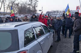 Protesters chant slogans while blocking a main road leading into the Moldovan capital during a protest in Chisinau, Moldova, Jan. 24, 2016.