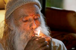 "Elections 2016 - Marijuana Emerald Triangle: In this Thursday, Oct. 13, 2016 photo, Swami Chaitanya lights a ""grower's joint"" marijuana cigarette at his home near Laytonville, California."