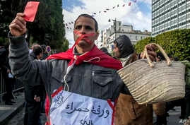"""A gagged Tunisian walks with an empty basket and a red card with a poster reading """"Red card to all politicians without exception"""" during a demonstration to mark the eighth anniversary of the democratic uprising in Tunis, Jan.14, 2019."""