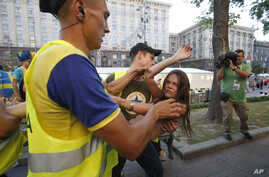 A protester from Ukrainian women rights  group Femen is carried away by security guards in the Kyiv fan zone during a protest in Kyiv against prostitution prior to the Euro 2012 soccer championship Group D match between Sweden and France, June 19, 20