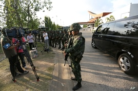 Thai soldiers stand in a line forcing journalists to stay in place after the military seized power at the Army Club in Bangkok, Thailand, May 22, 2014.