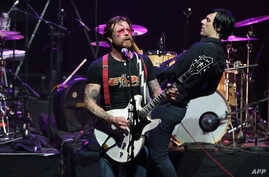 Jesse Hughes (L), the singer of US rock group Eagles of Death Metal, performs on stage at the Olympia concert hall in Paris, Feb. 16, 2016.