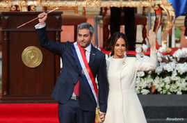 Paraguay's new President Mario Abdo Benitez gestures to the audience alongside Paraguay's first lady Silvana Lopez Moreira after being sworn in at the Lopez Palace in Asuncion, Paraguay, Aug. 15, 2018.