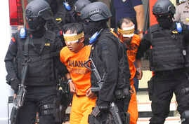 FILE - In this Feb. 21, 2016, file photo, Indonesian police officers escort suspected militants arrested in raids in Malang, East Java, Indonesia.