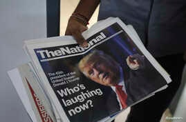 A man brings in newspapers with front page photos of President-elect Donald Trump at an office in Dubai, United Arab Emirates, Nov. 10, 2016.