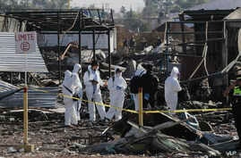 Soldiers and investigators walk through the scorched rubble of the open-air San Pablito fireworks market that exploded in Tultepec on the outskirts of Mexico City, Dec. 21, 2016. The market was especially well stocked for the holidays and bustling w