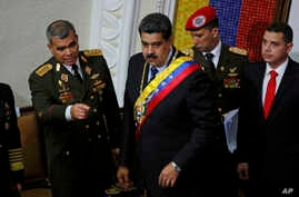 Venezuela's President Nicolas Maduro, center, stands with his Defense Minister Vladimir Padrino Lopez before giving his annual address to the nation to members of the Constitutional Assembly inside the National Assembly in Caracas, Venezuela, Jan. 14