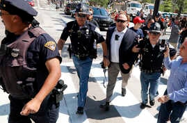 FILE - Alex Jones (C-R) is escorted by police out of a crowd of protesters outside the Republican convention in Cleveland, July 19, 2016.