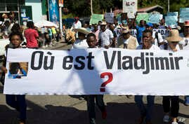 """Reporters hold a banner with a question that asks in French: """"Where is Vladjimir?"""" as hundreds of journalists marched to demand an investigation into why the 30-year-old photojournalist Vladjimir Legagneur vanished while on assignment, in Port-au-Pri"""