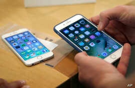 FILE - A  customer setting up his new iPhone 7 Plus (R) as he switches from the iPhone 6 at the Apple Store on Michigan Avenue, Chicago, IL., during the release of the Apple iPhone 7, Sept. 16, 2016.