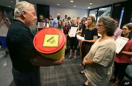 David Gray, left, director of external affairs at the Environmental Protection Agency Region VI office, accepts a barrel of letter from members of the Texas Campaign for the Environment at the EPA office in Dallas, Oct. 12, 2017. The letters to the E