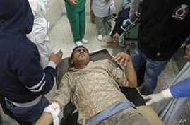 A wounded man is carried into the al-Jala hospital in Benghazi after an attack by Libyan military forces loyal to Muammar Gaddafi on a weapons dump near Benghazi in rebel-controlled eastern Libya killed 17 people, Al Jazeera television reported, Marc