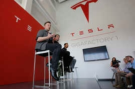 FILE - Elon Musk, CEO of Tesla Motors Inc., left, discusses the company's new Gigafactory in Sparks, Nevada, July 26, 2016. Tesla announced in September that it had been selected to build a battery storage project at the Mira Loma electricity substat