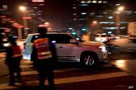An SUV drives past traffic police officers during evening rush hour in Beijing, Dec. 12, 2016. China's explosive demand for SUVs helped boost auto sales 17.2 percent in November over a year ago, an industry group said Monday.