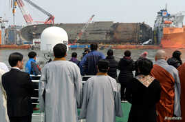 Family members of victims onboard the sunken ferry Sewol and religious people look on during a memorial ceremony at the sea off Jindo, South Korea, March 28, 2017.