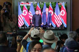 People watch a TV screen showing U.S. President Donald Trump, right, meeting with North Korean leader Kim Jong Un in Singapore during a news program at the Seoul Railway Station in Seoul, South Korea, June 12, 2018.