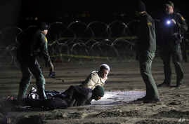 "FILE - In this Nov. 30, 2018 file photo, U.S. Border Patrol detain Honduran migrants after they walked onto U.S. territory from Tijuana, Mexico. Federal judges in California have challenged more of the Trump administration's ""zero-tolerance"" policy o"