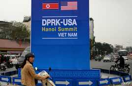 A motorist rides past a sign for the upcoming summit between U.S. President Donald Trump and North Korean leader Kim Jong Un, along a busy road in Hanoi, Feb. 19, 2019.