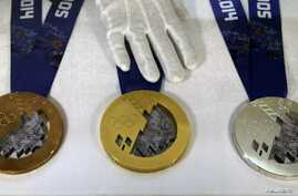 An employee arranges medals for the 2014 Winter Olympic Games during a presentation for the public at a jewellery shop in St. Petersburg September 19, 2013.