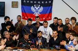 Pro-Russian separatist leader Denis Pushilin (C) talks during a media conference inside a regional government building in Donetsk, eastern Ukraine, May 8, 2014.