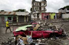 A man walks amid the debris of a destroyed car and buildings after the devastating earthquake in Pedernales, Ecuador, April 24, 2016