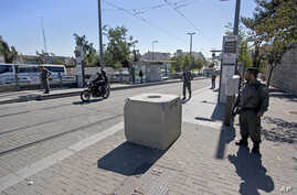 Israeli border police officers stand guard at the scene a day after a car ramming attack, in Jerusalem, Nov. 6, 2014.