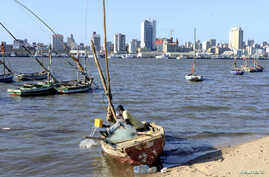 FILE - A fisherman cleans his boat beneath Maputo's skyline, Mozambique, August 15, 2015. A member of the Renamo party was killed October 8, 2016, on a Maputo beach.