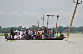 Villagers use a boat to cross a flooded road at Asigarh village in Morigaon district in the northeastern state of Assam, India, July 4, 2017.
