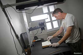 Photographer Jim Marshall, a member of the Foundation for the Preservation of Historical Heritage, photographs pages of a book in Bosnia's National Library in Sarajevo, Aug. 19, 2014.