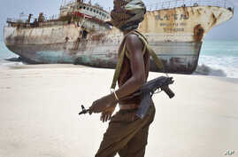 FILE -  Masked Somali pirate walks past a fishing vessel.