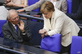 German Chancellor Angela Merkel, right, talks with Finance Minister Wolfgang Schaeuble prior to a debate about the British vote to leave the EU, in Berlin, June 28, 2016.