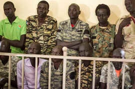 South Sudanese soldiers listen to the verdict being delivered at their trial in a military courtroom in Juba, South Sudan Thursday, Sept. 6, 2018.
