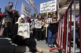 FILE - Women hold pictures of relatives who went missing during Lebanon's civil war, which took place from 1975 to 1990, during a protest in front of the government palace in Beirut, Sept. 18, 2014.