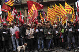 Pro-independence demonstrators of Catalonia and Basque Country raise their regional flags as they gather on a square to support an informal independence poll to celebrate in Catalonia, in Pamplona northern Spain, Nov. 9, 2014.