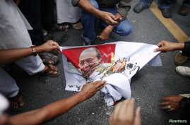 Muslims burn a picture of Myanmar's president Thein Sein as they protest in front of Myanmar's embassy in Bangkok, June 21, 2012.