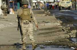 Army soldiers gather at the scene of a bomb attack in Baghdad, Iraq, Saturday, Nov. 26, 2011.