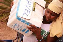 A woman helps load relief supplies onto a truck bound for northern Mali, April 13, 2012. (N. Palus/VOA)